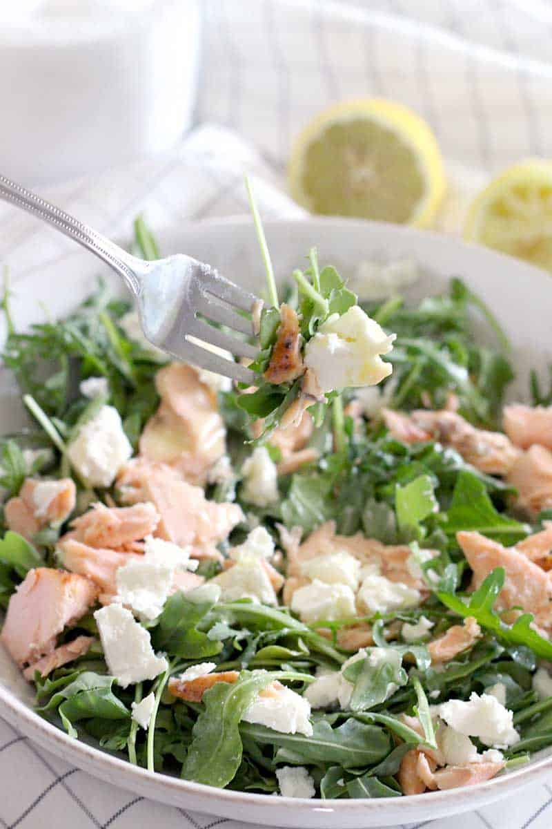Salmon, Goat Cheese, and Arugula Salad with Creamy Lemon Garlic Dressing! Use up cold leftover salmon in this simple, easy salad. The dressing is AMAZING, and has a secret ingredient that helps emulsify it and add a creamy texture with no dairy!