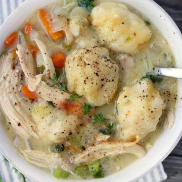 a close up photo of a bowl filled with chicken and dumplings and a spoon