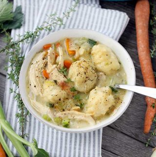 A bowl full of chicken and dumplings with a spoon and vegetables in the background
