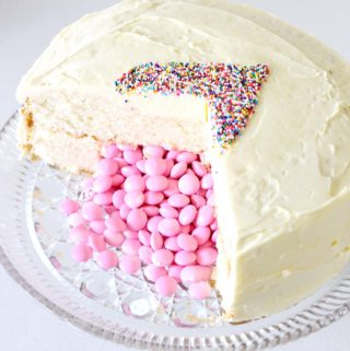 A step by step tutorial for an adorable, pink (or blue) M and M chocolate candy filled white cake with a sprinkle heart that reveals the baby's gender!