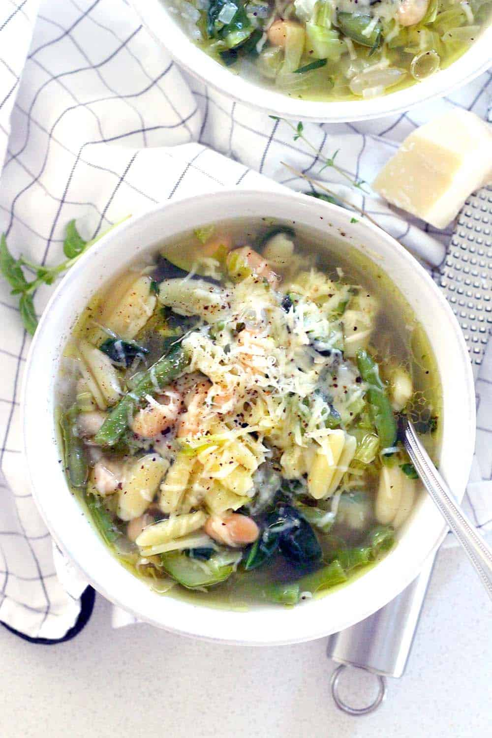 This minestrone soup is PACKED with healthy green veggies, fresh herbs, and topped with a drizzle of olive oil, Parmesan, and pepper. It comes together in 30 minutes and is freezable.