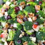 Close up photo of a bowl of broccoli salad with apples, walnuts, and cranberries.