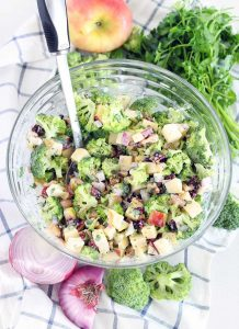 This broccoli salad with apples, walnuts, and cranberries is sweet, crunchy, and tangy. It's the perfect healthy thing to take to a potluck or picnic, since it doesn't get soggy and it makes a ton! Paleo, dairy free, gluten free, and vegetarian.