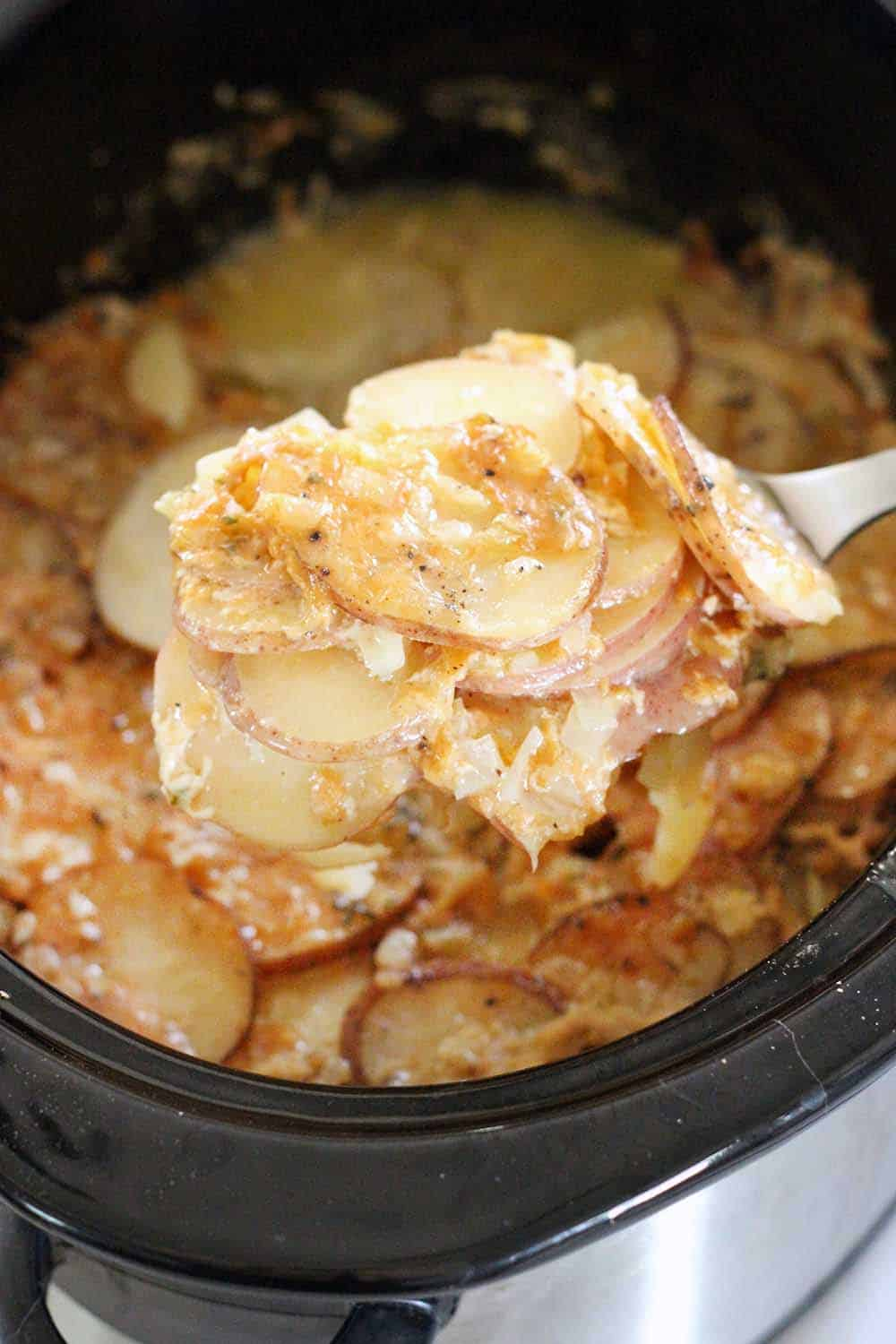 These Slow Cooker Scalloped Potatoes are rich and creamy and smothered in Gruyere and Parmesan cheese. It's the perfect thing to make for Thanksgiving dinner because it frees up space in your oven and on your stove top!