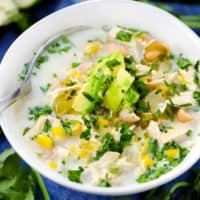 A white bowl filled with white chicken chili topped with avocado and cilantro.