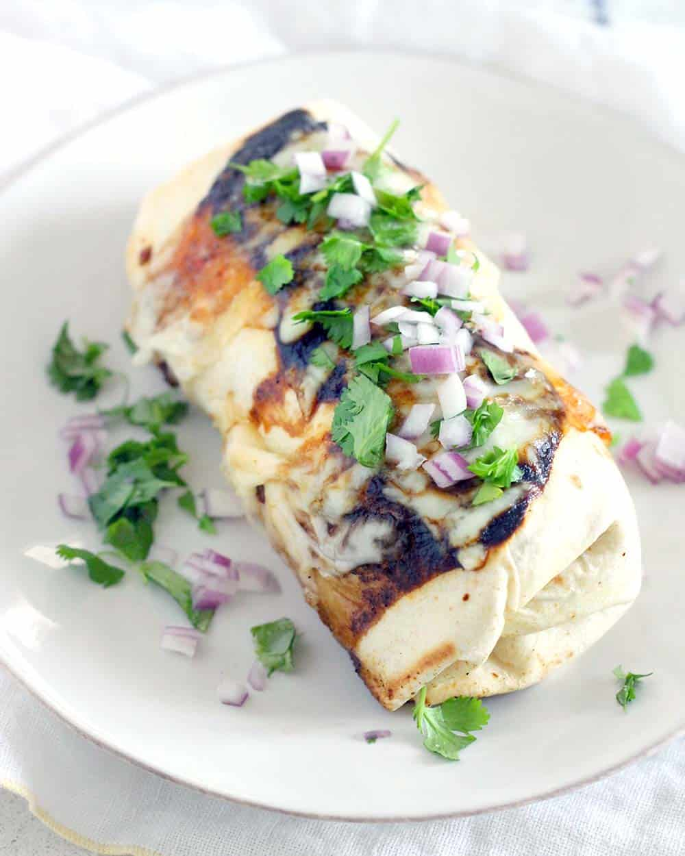 This Baked Chipotle Chicken Burritos recipe is smoky and bursting with flavor. They are easy to assemble ahead of time and covered with chipotle sauce and melty cheese, just like at your favorite Mexican restaurant!