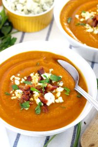 This Smoky Sweet Potato Soup is topped with crunchy bacon and tangy bleu cheese crumbles- an easy and DELICIOUS recipe for cold winter and early spring evenings! Vegetarian/vegan/Paleo optional.