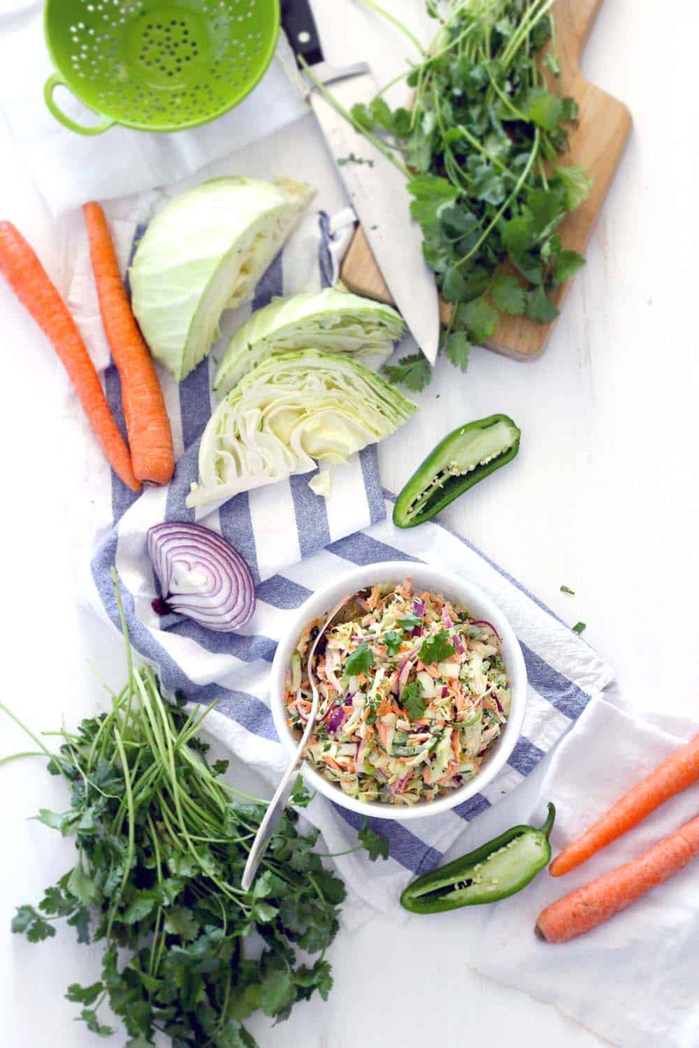 This easy, delicious recipe for Spicy Jalapeno Cilantro Slaw is great as a side, or on top of your favorite pulled pork sandwiches or fish tacos! Vegetarian, vegan optional, low carb, and paleo compliant.