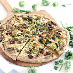 Brussels Sprout and Bacon Pizza is a match made in heaven and a FOUR INGREDIENT recipe! A white pie with seared brussels sprouts, crunchy bacon, and mozzarella cheese baked on a cast iron pizza pan until bubbly with a whole wheat crust. YUM.