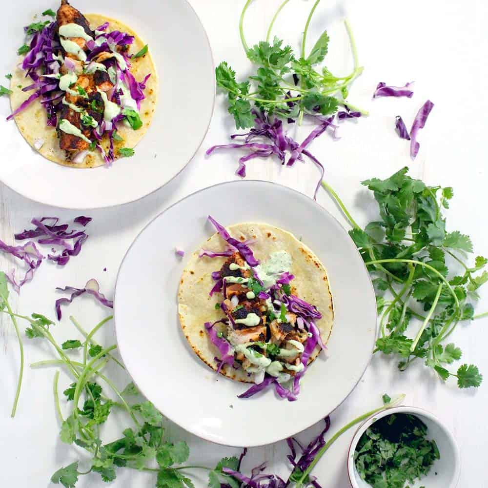 These Chipotle Salmon Tacos with Cilantro Lime Crema come together in only 15 minutes! The spicy chipotle flavor is balanced by the cool crema. This is my FAVORITE fish taco recipe.