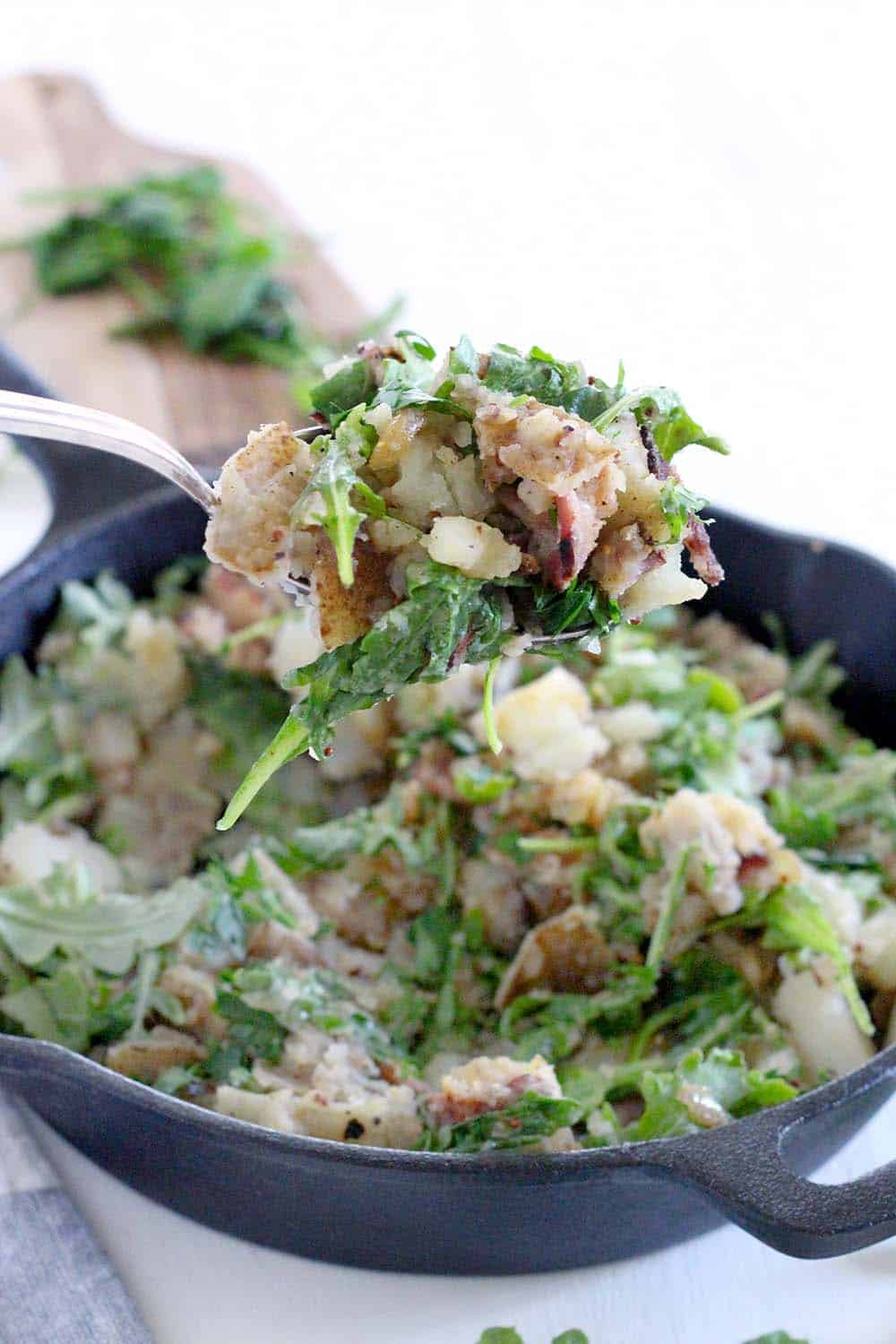 This Skillet Potato Salad with Bacon and Arugula recipe is served warm with a sweet and tangy vinegar-based dressing. It's similar to German potato salad, Paleo and gluten-free, and the perfect side dish all year round!
