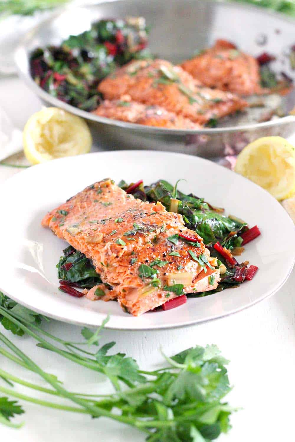 One Pan Garlic Butter Salmon and Swiss Chard- This healthy, gluten-free, low-carb recipe comes together in only 20 minutes! Can easily be made paleo or whole30 compliant by using ghee instead of butter.