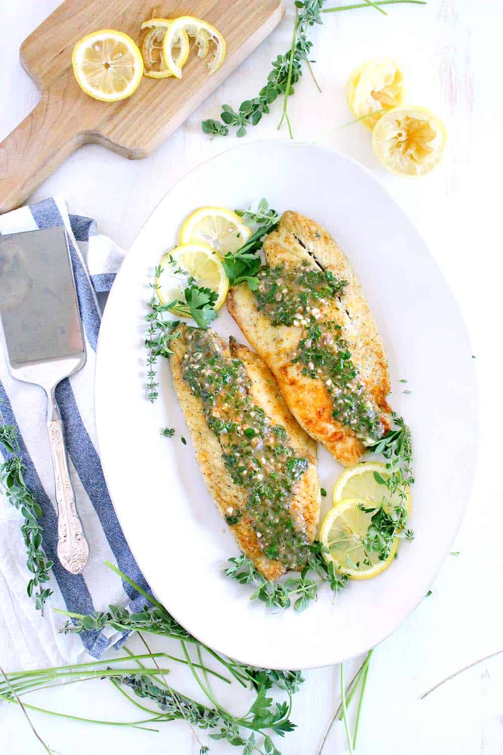 An overhead photograph of a platter of sea bass with lemon slices and a garlic herb sauce with a serving spatula.