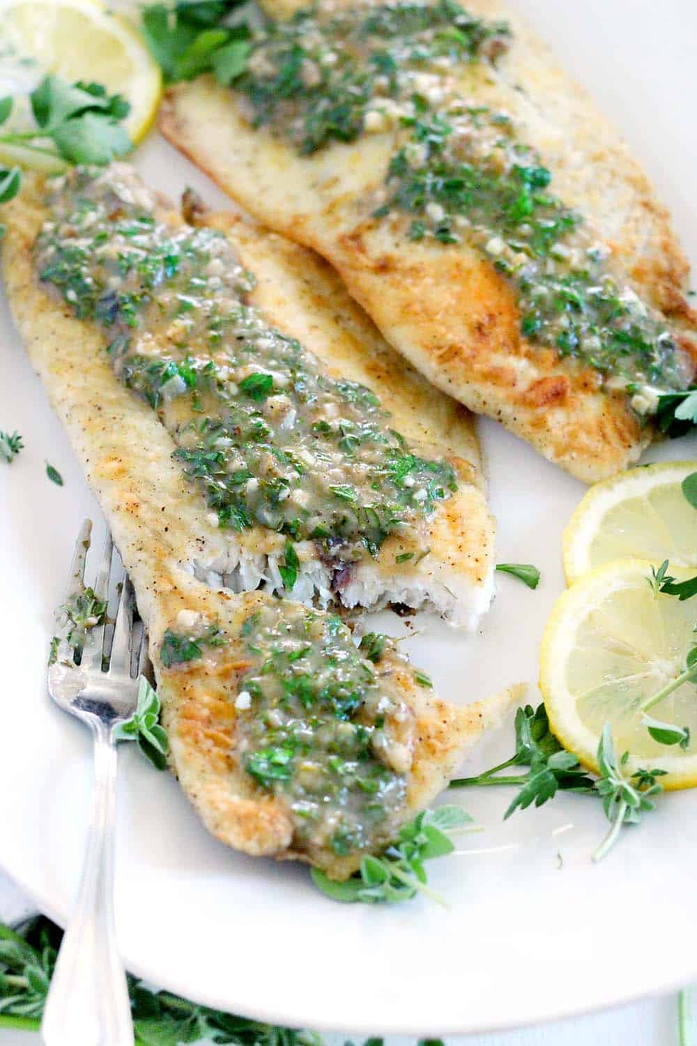 This pan fried sea bass with lemon garlic herb sauce is packed with flavor from fresh herbs. It's a delicious 20 minute meal that's perfect for feeling fancy on a busy weeknight!