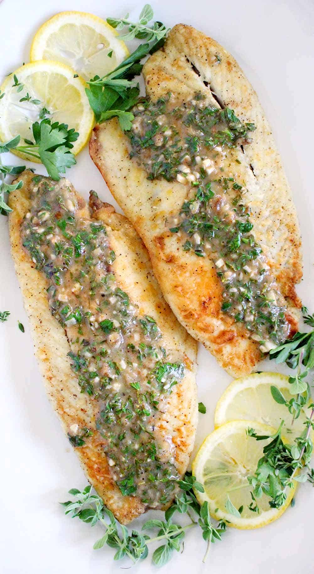 A close up photograph of pan fried sea bass with lemon garlic herb sauce