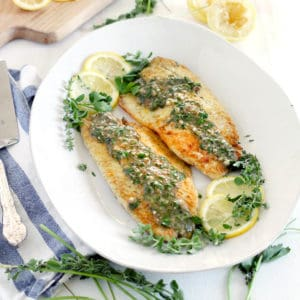 A platter of pan fried fish with herb sauce and lemon slices.