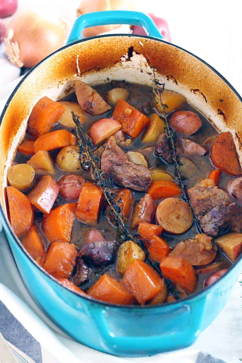 This simple Irish Lamb and Potato Stew is cooked in a dutch oven and is warm and comforting during cold weather. Sweet potatoes and dark beer are added for amazing depth of flavor, with no flour needed as a thickener. Easily adaptable to be paleo/whole30 compliant! #IrishFood #Paleo #LambStew