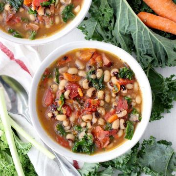 Overhead photo of two bowls of instant pot black eyed pea soup with kale and carrots.