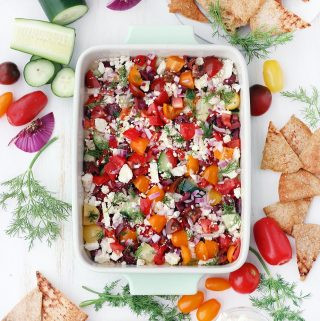 This Mediterranean Seven-Layer Dip recipe is fresh and delicious! It's the perfect snack to serve with pita chips. No cooking required! It's packed with hummus, fresh veggies, olives, and feta and it's super easy to assemble. #MediterraneanDiet #Vegetarian #Appetizers #NoCookRecipes #SevenLayerDip #GlutenFreeSnacks