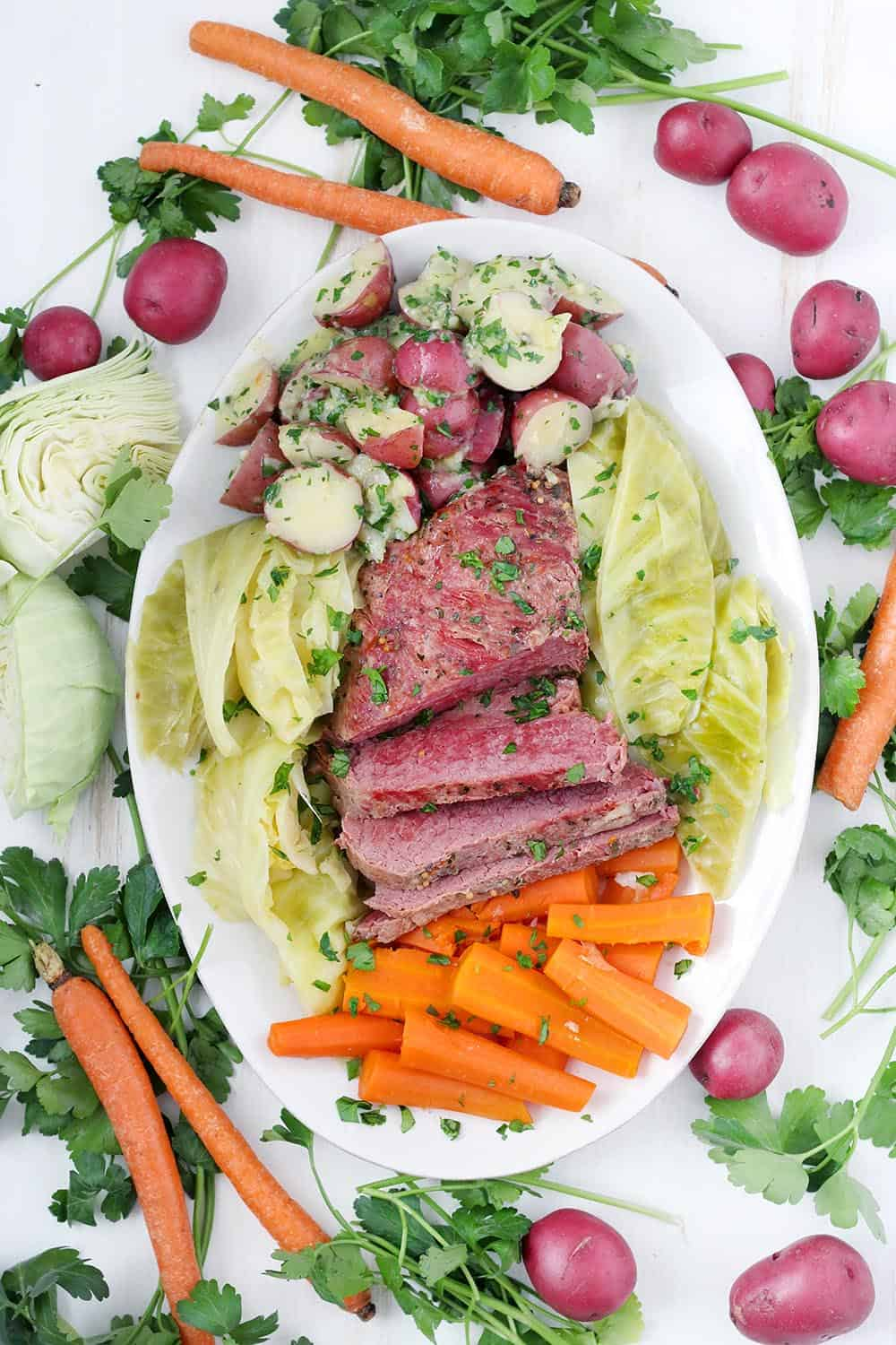 Celebrate St. Patrick's day with this recipe for Instant Pot Corned Beef with Cabbage, Carrots, and Buttered Potatoes! It takes half the amount of time as on the stovetop when you use a pressure cooker. The best part is the potatoes, smothered in melted butter and fresh parsley, and the corned beef is perfectly cooked to a fall-apart texture.