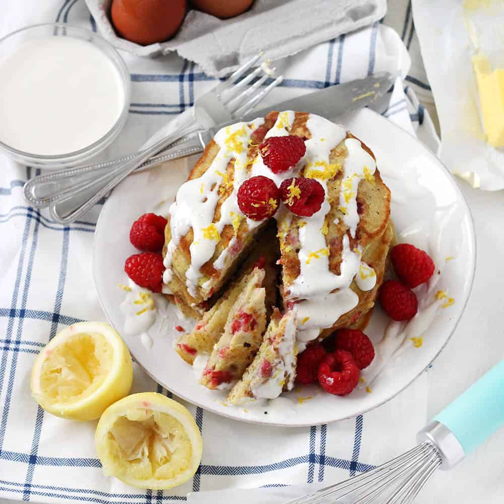These refined sugar free Lemon Raspberry Pancakes are topped with a creamy Maple Cream Cheese Drizzle. They are light and tart and fluffy- and the red and yellow colors are so pretty! This is the perfect weekend breakfast recipe.