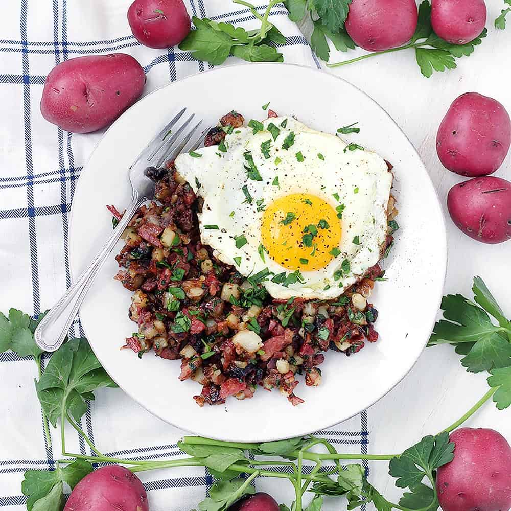 This one-pot Corned Beef Hash recipe is made with raw potatoes, unlike most other hash recipes. This is a simple recipe made with potatoes, onions, butter, parsley, and corned beef. Serve with sunny-side-up or fried eggs for a delicious breakfast!