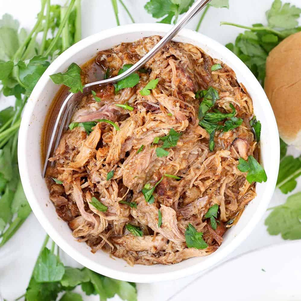 A bowl of pulled pork with a spoon garnished with cilantro