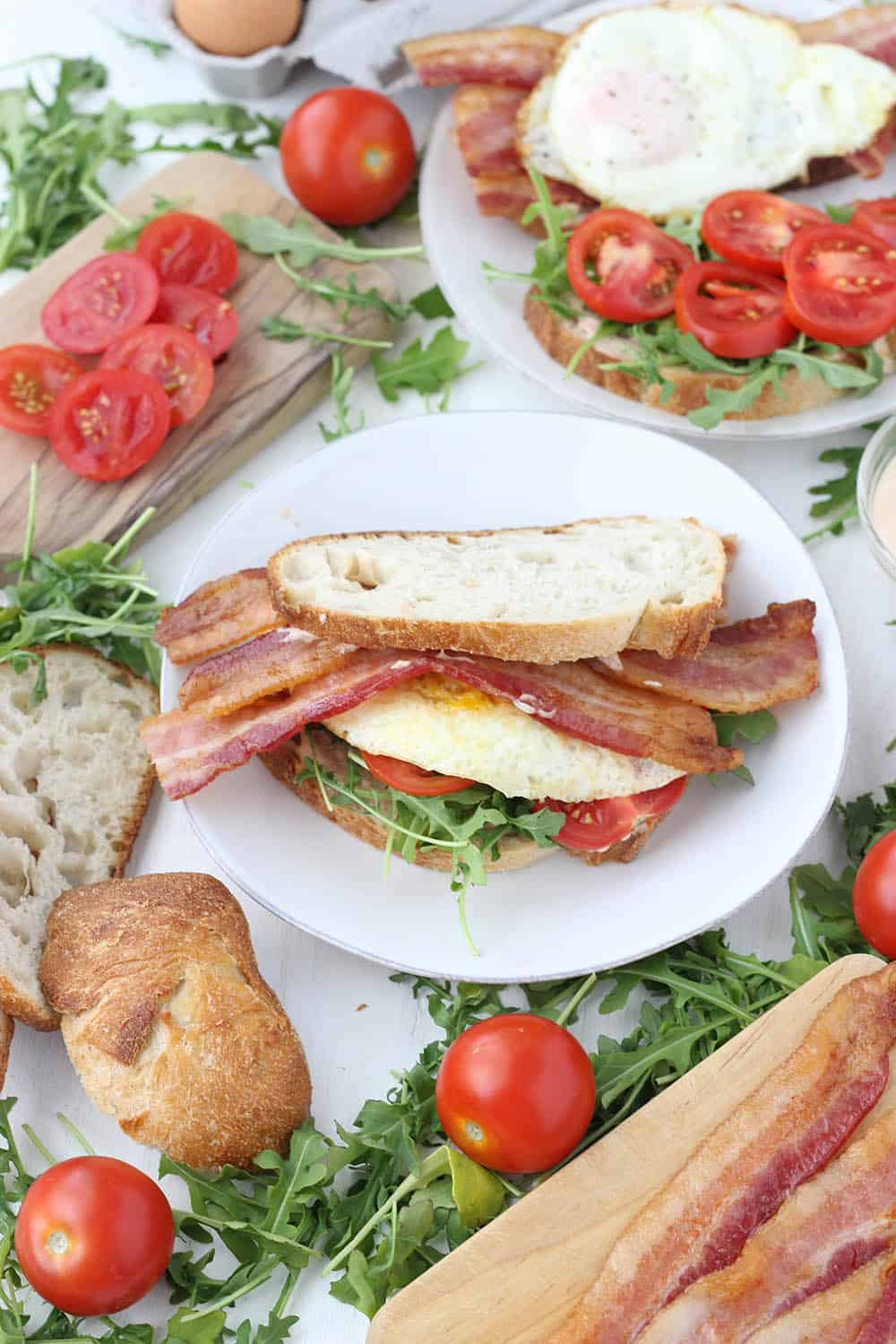 These Breakfast BLTs with Spicy Mayo and Arugula are piled high with thick-cut bacon and a perfectly fried egg! Bake the bacon in the oven to easily make these for a crowd.