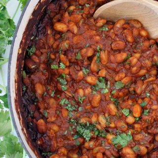 These Mexican Baked Beans with Chorizo are smoky, sweet, and spicy! This gluten free recipe makes a TON, and it's freezable. Serve as a side at your next BBQ, piled on toast, or with fried eggs for brunch.
