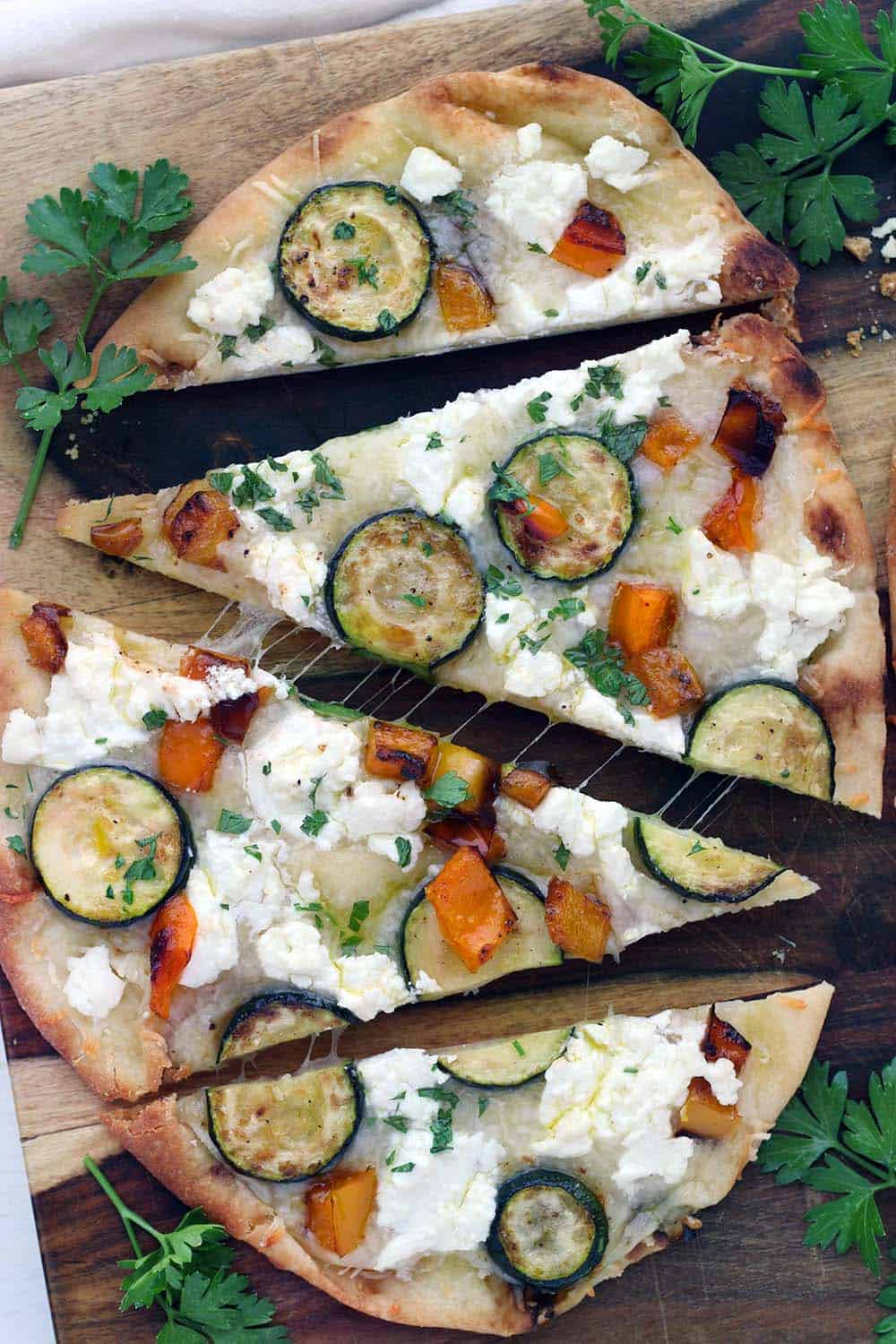 This vegetarian Sautéed Vegetable and Goat Cheese Naan Pizza recipe comes together in only 20 minutes for an easy weeknight dinner! Tip: place the baking rack in the lower half of the oven for a crisp crust.