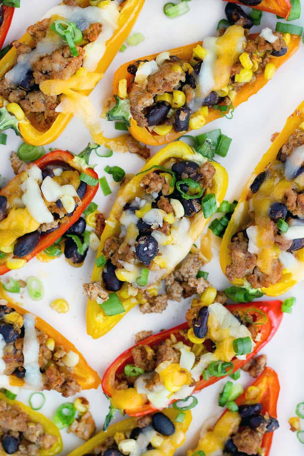 These Taco Stuffed Mini Peppers are the perfect appetizer or light meal! The sweet mini peppers are filled with slightly spicy, taco flavored ground turkey, black beans, and corn for a super fun, low-carb finger food.