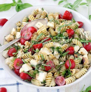 This fast and easy Caprese Pasta Salad recipe is coated in a light, creamy balsamic and olive oil dressing. A great vegetarian weeknight dinner, or add grilled chicken to make it more hearty.