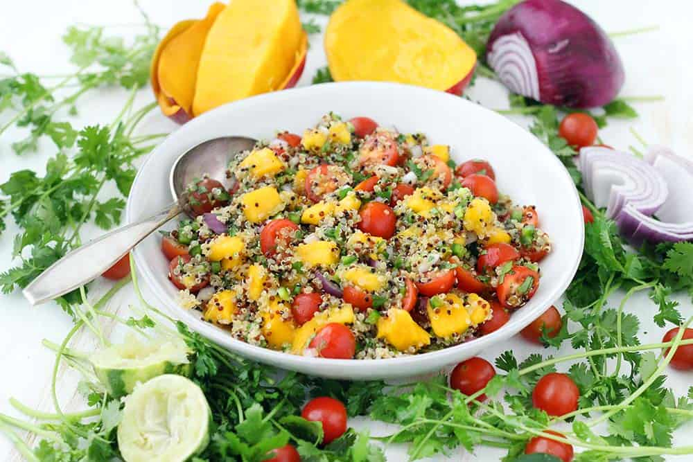 Served cold, this refreshing Mango Quinoa Salad is the perfect sweet/spicy balance, with jalapeños, cilantro, onion, and tomatoes. Make this vegan recipe ahead of time and serve straight out of the fridge! It's amazing paired with a spicy protein, like blackened tilapia or jerk chicken.