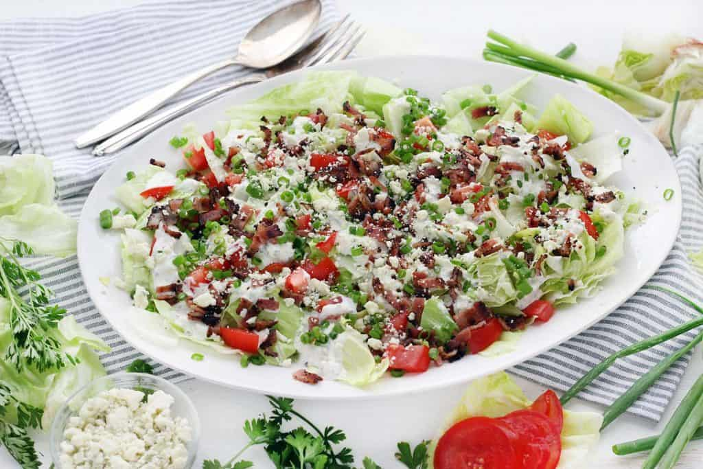 This Deconstructed Wedge Salad recipe has all the classic, refreshing flavor without the need for a knife! Chopped iceberg lettuce is drizzled with homemade blue cheese dressing and topped with crunchy bacon, green onions, and fresh tomatoes.