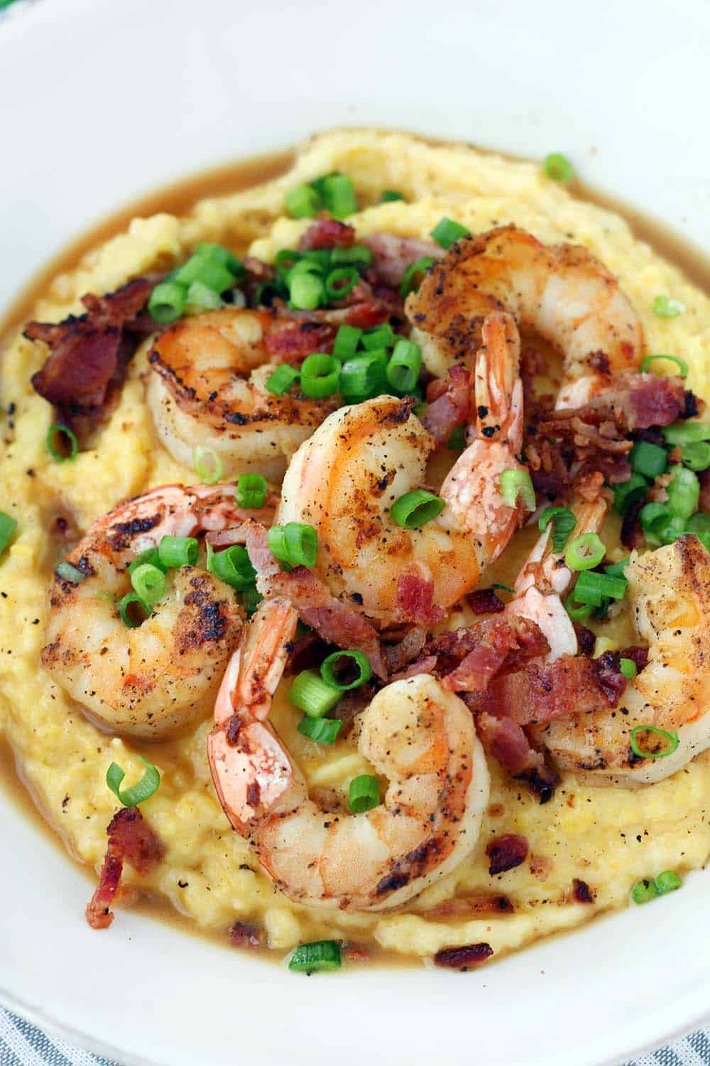 This classic Shrimp and Grits recipe is easy to make and is such delicious Southern comfort food! The cheesy grits are cheap and gluten free, and make an excellent base for the flavorful shrimp and crumbled bacon.