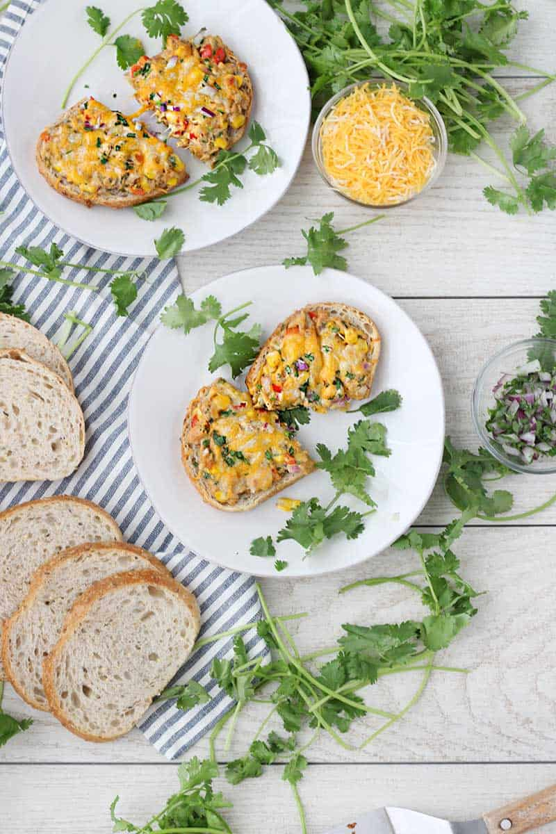 Tex Mex Tuna Melts are such a fun twist on a classic! Corn, bell peppers, jalapeño, cilantro, and onion are mixed in tuna, spread on bread, and topped with Mexican cheese, then baked until melty. Such an easy weeknight dinner recipe!