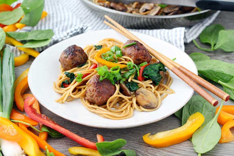 A white plate with meatball lo mein, veggies around it, and chopsticks.
