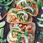 Chicken Banh Mi Tacos are bursting with fresh Vietnamese flavor. Marinated chicken thighs and pickled veggies, wrapped in toasted corn tortillas, topped with a spicy mayo and cool cucumber and herbs! This is an easy, gluten free recipe.