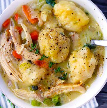 Square photo of chicken and fluffy drop dumplings close up in bowl.