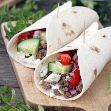Close up photo of Greek lamb tacos with cucumbers and Tzatziki sauce.