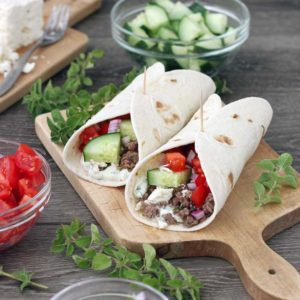 Square photo of two lamb tacos with lamb and vegetables.