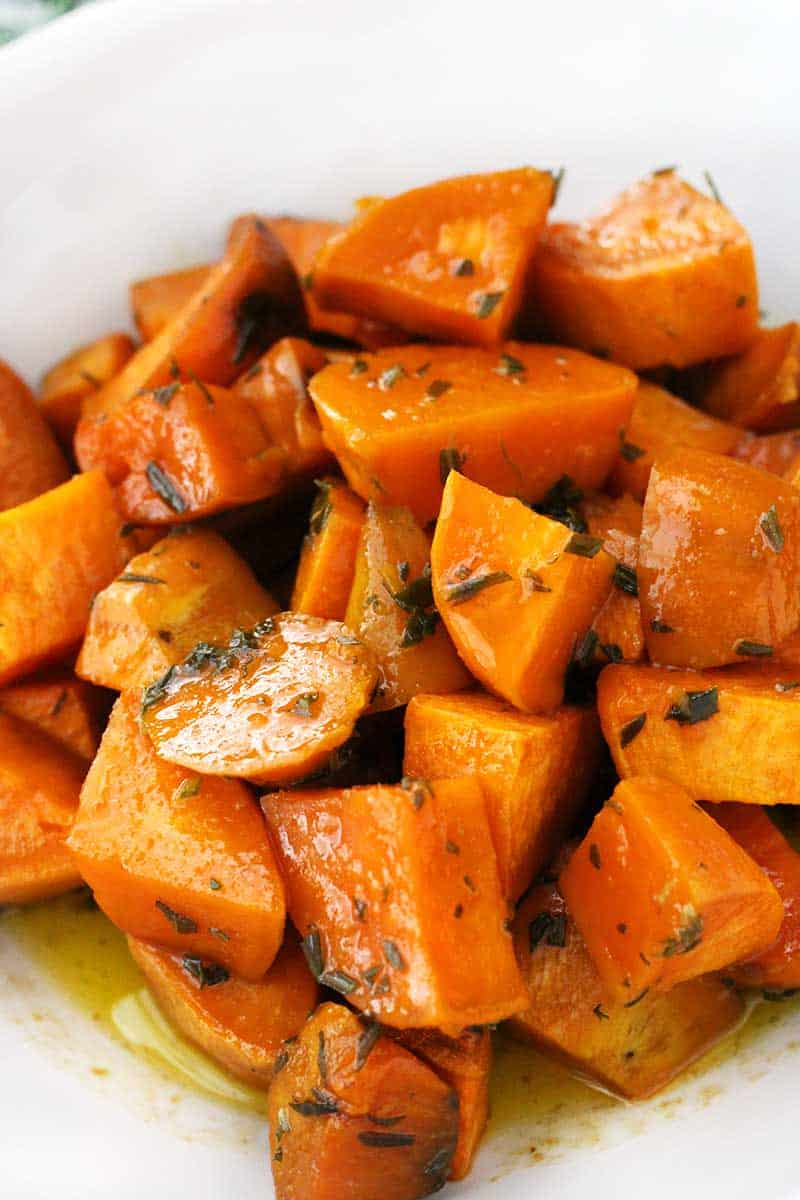 These Glazed Sweet Potatoes are coated in a mixture of melted butter, fresh rosemary, and maple syrup, then baked in the oven until super tender. They're not too sweet, and they're the perfect vegetarian, gluten-free side dish!