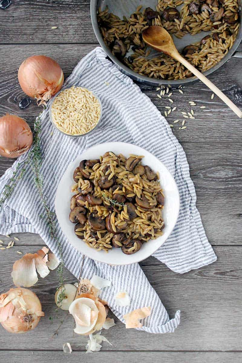 Orzo with Mushrooms on a white plate and a sprig of thyme with onions, thyme, and orzo in the background and a skillet with a wooden spoon