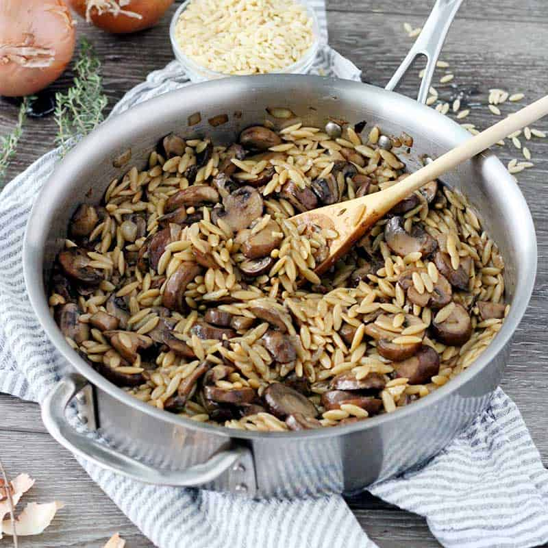 Orzo with Mushrooms in a skillet with a wooden spoon