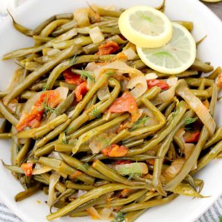 These Greek Green Beans (Fasolakia) are velvety tender, served in a tomato and garlic based sauce with lemon, dill, and plenty of extra-virgin olive oil. It's a great Mediterranean, low carb, paleo, and vegan side dish!