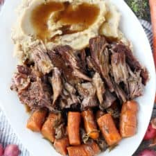 A platter with pot roast, mashed potatoes, carrots, and gravy overhead shot