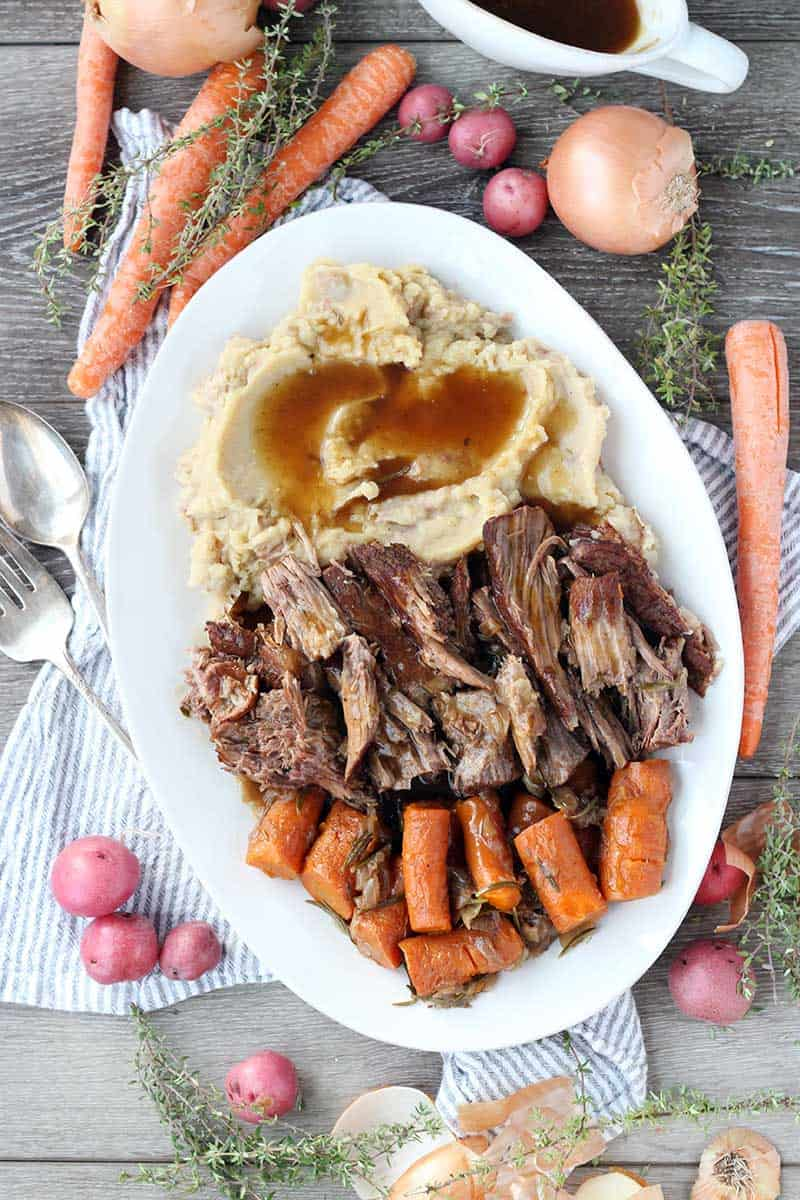 A platter with pot roast, carrots, mashed potatoes, and gravy