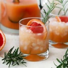 A greyhound cocktail with fresh rosemary and a slice of grapefruit.