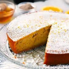 Orange olive oil cake with a slice taken out.