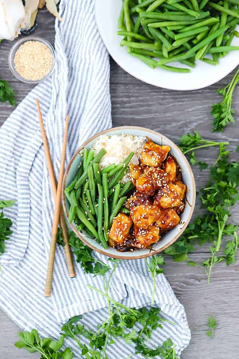 Overhead photo of a bowl of sesame chicken on a striped towel with green beans and chopsticks around it.